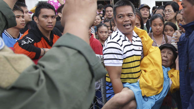 Filipino troopers control survivors who want to board military planes to flee the typhoon ravaged Tacloban city