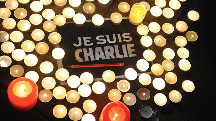 Candles are placed next to a sign reading 'Je suis Charlie' (I am Charlie) and a pen in La Rochelle on January 7, 2015, as people gathered to pay tribute to the twelve people killed in an attack by two armed gunmen on the offices of French satirical newspaper Charlie Hebdo in Paris. (AFP Photo/Xavier Leoty)